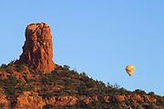 Chimney Rock and hot air balloon at sunrise; Sedona, Arizona.