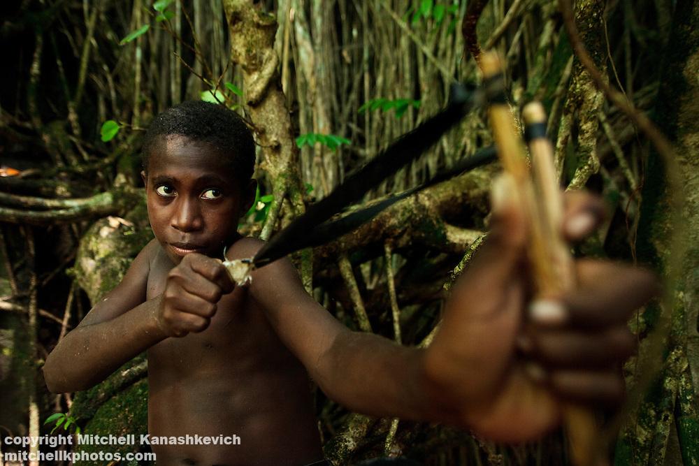 Ni Vanuatu boy hunting flying foxes and birds with a sligshot. Rah Lava Island, Torba Province, Vanuatu