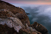 A temporary clearing in thick fog at sunset, caused by a major temperature inversion, seen here at South Stack, Irish Sea, North Wales. The RSPB information centre and viewing point of Elim's Tower is the white building on the cliff top.