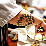 "SHOT 2/17/12 7:19:13 PM - A skull tattoo on the arm of a chef at TAG  restaurant on Larimer Square in downtown Denver, Co. TAG is operated by chef/owner Troy Guard. TAG features what they term ""continental social food"" and features influences from numerous continents. Tattoos are definitely part of the ""look"" of the restaurant that also features an alternative playlist many evenings and Vans sneakers for much of the wait staff..(Photo by Marc Piscotty / © 2012)"