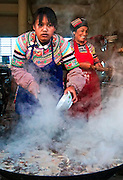 Cooking up a giant potfull ina village in Yuanyang, China.