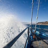 Norway, Svalbard, Nordaustlandet, Yacht SV Arctica sailing through heavy seas in Hinlopen Strait on summer evening