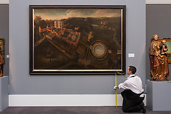 Sotheby's London, November 28th 2014.Sotheby's hold a preview for their December 3rd sale of Old Master and British Paintings at their Bond Street gallery. The exhibition runs from November 29th to December 3rd. PICTURED: A Sotheby's gallery technician takes  measurements of to ensure that the first bird's eye view of a British Estate, a view of Llanerch Park, Denbeighshire is hanging correctly. This painting established a tradition of bird's-eye-views of British country houses and is expected to fetch up to £600,000.