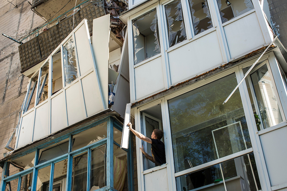 A man begins cleaning up the damage at an apartment building that was hit by a supsected grad rocket strike on Tuesday, July 29, 2014 in Donetsk, Ukraine.