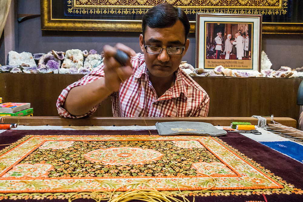 A man creating an embroidered Zardozi wall hanging , Agra India.