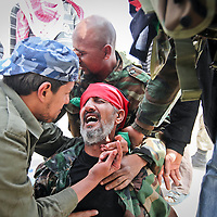 The brother of a rebel fighter severly injured by an explosion during clashes with government troops weeps outside of Ajdabiya, 100 miles south of Benghazi, Libya. March 2011.