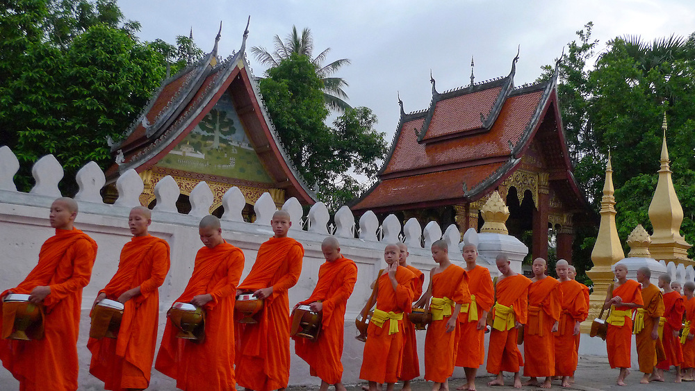 Young monks walking in Luang Prabang for the ealy monring alms. Copyright Martine Perret