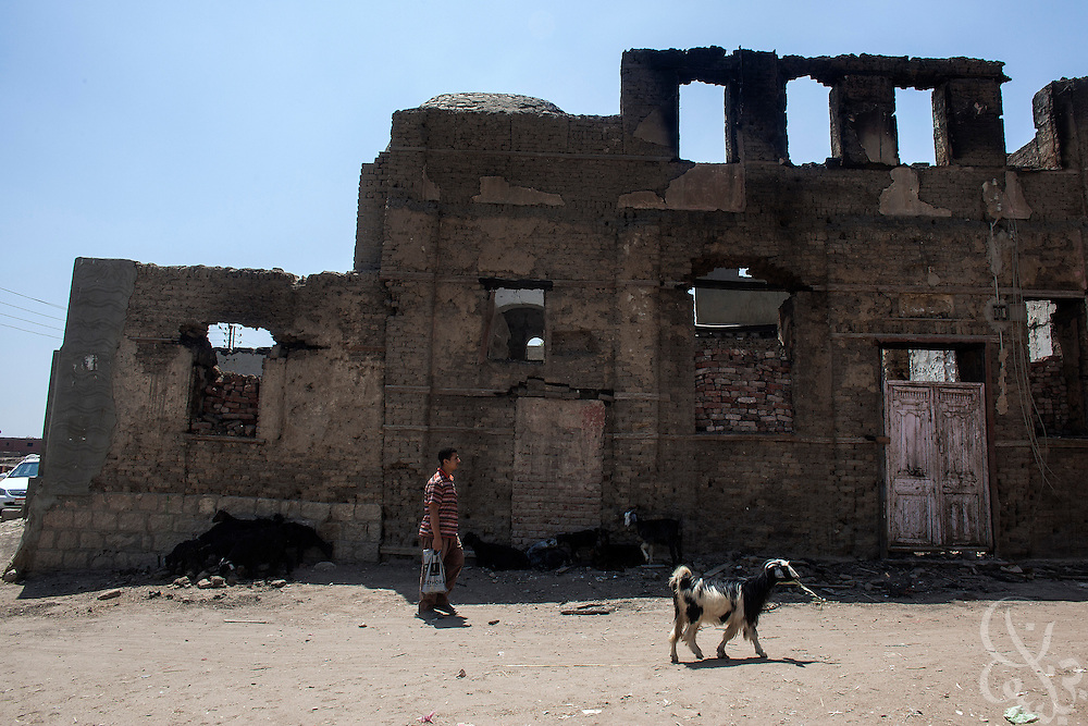 An Egyptian man walks past the burnt and looted ruins of the (old) Virgin Mary Church August 20, 2013 in the village of Nazla, located near el Fayoum, and around a 100 kilometers South of Cairo, Egypt.  Christian villagers report 2 churches and a monastery in the area came under attack by their Muslim neighbors on the same day as Egyptian security forces were moving to forcibly disperse the sit-in camp of the supporters of deposed president Mohamed Morsi.