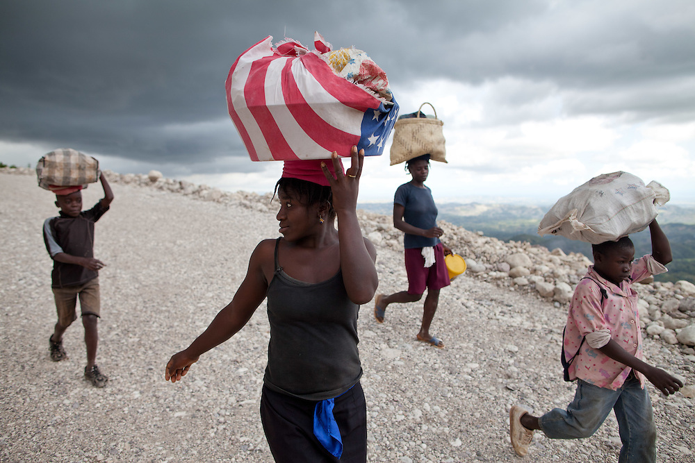 Women and boys walk home to Camp-Perin after doing business in a market  several hours away. They say they are walking because riding on a truck is too expensive. The Inter-American Development Bank is funding this road project in the south of Haiti, aiming to cut travel time and transportation costs, and to improve living conditions in the southern provinces. This 50-mile stretch of road connects the small cities of Les Cayes and Jeremie and many rural villages in between. A Brazilian company, OAS, is doing the construction. The road is far from complete, but is already transforming commerce and daily life in the area. Travel time has been cut in half; fewer trucks are breaking down, so less food is spoiled; and farmers are planting more crops in anticipation of more dependable farm-to-market transportation.