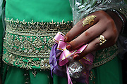 The hand of Afghan bride Mushgar,19, is adorned with the tradional bridal gold jewelry and her hands are decorated with Hena during the wedding ceremony in the neighborhood of Golbahar outside of Kabul Afghanistan April 17,2004.Marriges in Afghanistan are commonly arranged between families and not by the yound people themselves. In arranging a marriage families take several factors into account:sectarian membership,ethnic group,family status, kin relationship, economic benifits, and (in obtaining  a bride) industriousness and ability to cooperate with the groom's female realations.Women were, after marriage, viewed as the husband's family's prperty to the extent that if her husband died she was forced to marry his brother or next to kin.Tribal laws viewed marriages as alliances between groups:women were pawned into marriages, not allowed to divorce, total obedience to the husband and his family was expected nad they were prevented from getting any education.
