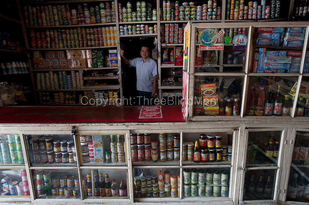 The 'Modern Store'. <br /> Chinese owned old corner store. Mr. Andre Lam , the owner, stands in a doorway.