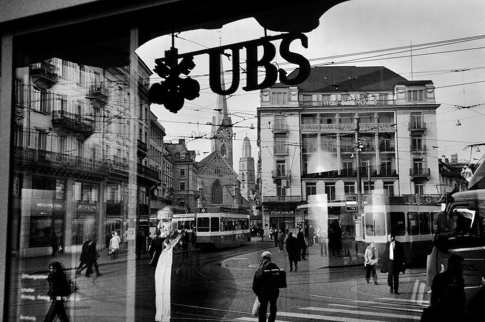 Paradeplatz, Zurich's Wall Street, symbolic centre of the Swiss banking industry, reflected in the entry to UBS, Switzerland's largest bank. UBS, considered 'too big to fail' was bailed out by the Swiss government following record losses for a Swiss company following excessive exposure to the U.S. subprime market.
