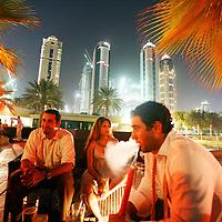 Hamza Abu Zanad, 27, from Jordan, right, smokes shisha with friends at an exclusive bar in Dubai. August 2008.