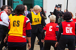 Ealing, London, December 9th 2014. Mayor of London Boris Johnson visits Ealing, Hammersmith and Fulham College accompanied by   Deputy Mayor for Policing and Crime Stephen Greenhlagh to launch a new initiative to increase black and ethnic minority applicants to the Met. PICTURED: Resplendent in a Yellow bib, Mayor of London Boris Johnson participates in an impromptu game of netball with college students.
