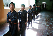 Boys leave class for their rooms and a change of clothes before prayer at the mosque...In a country of some 160 million people, affordable education is beyond the reach of most parents in Pakistan. An education is considered a luxury to most people living in the slums of major cities and the rural areas of Pakistan. At an Edhi Boys Home some 56km outside Karachi 200 boys are offered a basic education and temporary home for up to 5 years. They are gain basic skills in literacy, numeracy,  English and Urdu. ..The facility provides a number of recreational facilities such as football and cricket as well as an on-site mosque. The facility relies solely on voluntary donations and is independent of government and commercial influence. ..The Edhi foundation was established by Abdul Sattar Edhi. Born in a small Indian own of Bantva in the province of Gujrat he migrated to Pakistan during partition in 1947. After working as a commissioning agent selling cloth in a market in Karachi Abdul Sattar Edhi and other members of his community decided to establish a free dispensary in the city. Disillusionment with the lack of health care led him to establish a welfare trust of his own called the Abdul Sattar Edhi Foundation. Appeals were made, funds raised and soon a home was established and a number of ambulances patrolled the streets of Karachi...In 1965 Adbul married a nurse working at the foundation, Bilquis. They have four children and all are involved in the current day to day running of the foundation. Bilquis Edhi runs a maternity home at the headquarters in Karachi and organises the adoption of illegitimate children and abandoned babies. The family share the foundation's vision of a single minded devotion to the cause of alleviation of human sufferings and a sense of personal responsibility. The foundation responds for calls of help from ordinary people, regardless of race, creed or status and now provides a priceless welfare service to the people of Pakistan...The foundatio