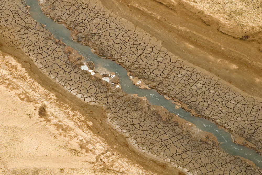 La Mer Morte, alimentée par le Jourdain, est un lac d'eau salée d'une surface approximative de 810 km2, partagé entre Israël, Jordanie et Territoires Palestiniens occupés. Au point le plus bas du globe à 417 mètres sous le niveau de la mer, la salinité de la Mer Morte est de 27,5 %  et son niveau d'eau baisse d'un mètre par an en moyenne. Le dessèchement est tel qu'une large bande de terre craquelée la scinde désormais en deux bassins distincts. La cause essentielle en est la surexploitation croissante du Jourdain à des fin d'irrigation. Une autre cause considérable est l'évaporation de volumes importants d'eau menée par les usines de Dead Sea Works pour la production de produits à base de potassium. Écologie, économie et géostratégie y sont continuellement un peu plus fragilisés. Israël, mai 2011