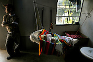 Newborn Erik Orlando Hernandez Ruiz, 2 months, hangs from the rafters in a crib made from wire and a bag of corn, his father, Adam Hernandez Ruiz, stands at the door. Xicalcal, Guatemala.