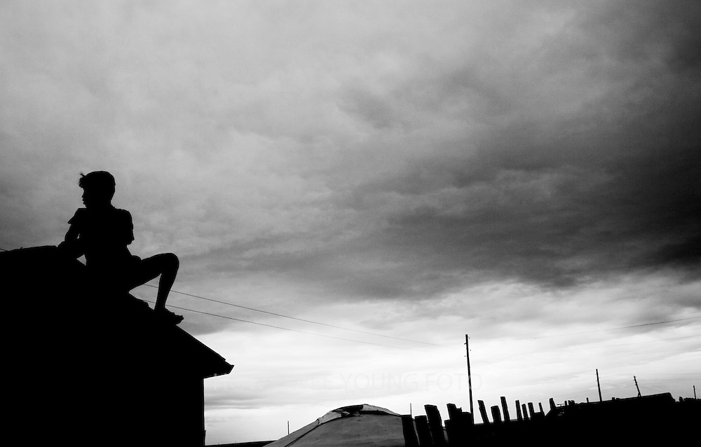 A young Mongolian boy views the desolate landscape from a rooftop in his town in Mongolia.