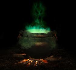 bubbling iron cauldron with green smoke and evil spirit rising