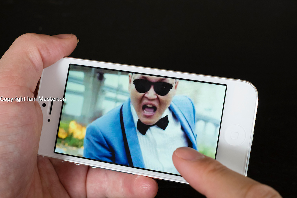Close-up detail of man holding new iPhone 5 smart phone showing iTunes music store with video by PSY of Gangnam style