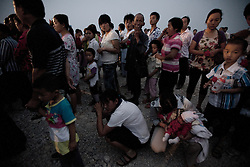 Migrant villagers of Cangfang village gather for relocation to neigbouring Hui county to make way for the colossal South-to-North Water Diversion (SNWD) project in Xichuan county of Henan Province in China on 29 June 2010. The central route, which will raise the height of the Danjiangkou reservoir dam from 162 meters to 176.6 meters, requires the relocation of 330,000 people in Henan and Hubei provinces. Xichuan, a remote, mountainous region inaccessible by railway, is home to 162,000 would-be SNWD migrants, the most anywhere. The SNWD project, the largest known water diversion project, was started in 1952 to solve the country's chronic water shortages and involves creating three routes to channel 44.8 billion cu m of water from southern China to the northern areas. As part of the project's central route, affecting Henan and Hubei provinces, water from the Danjiangkou Dam reservoir will be diverted to Beijing.