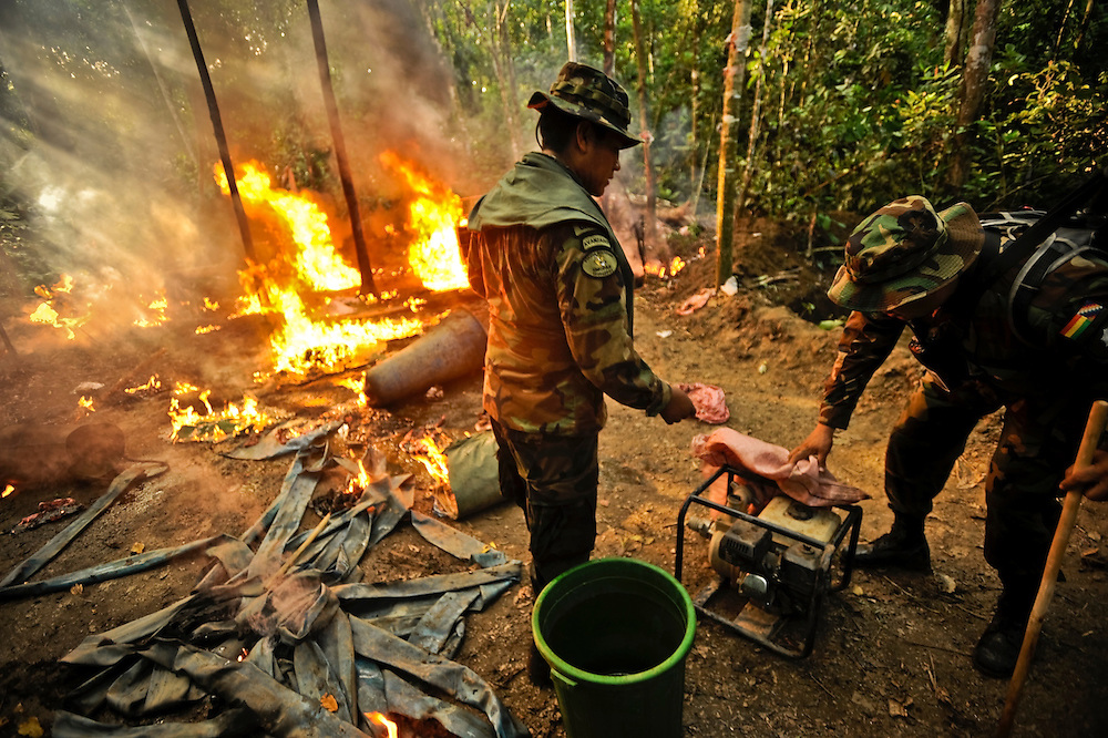 "Bolivian FELCN Special Forces police, Juan Pablo Claros López, 25, (left) and Lt. Coronel René Ronaldo Gómez Guzman (right) burn and destroy a cocaine-base processing lab in the thick, tropical outskirts of Villa Nuevo Horizonte, a dangerous area in the department of Santa Cruz were narcotraffiking runs rampant. FELCN officials report it is the area of Bolivia most thickly dense of narcotraffickers and cocaine-base processing laboratories.  FELCN police commonly referred to it as a ""narco pueblo""."