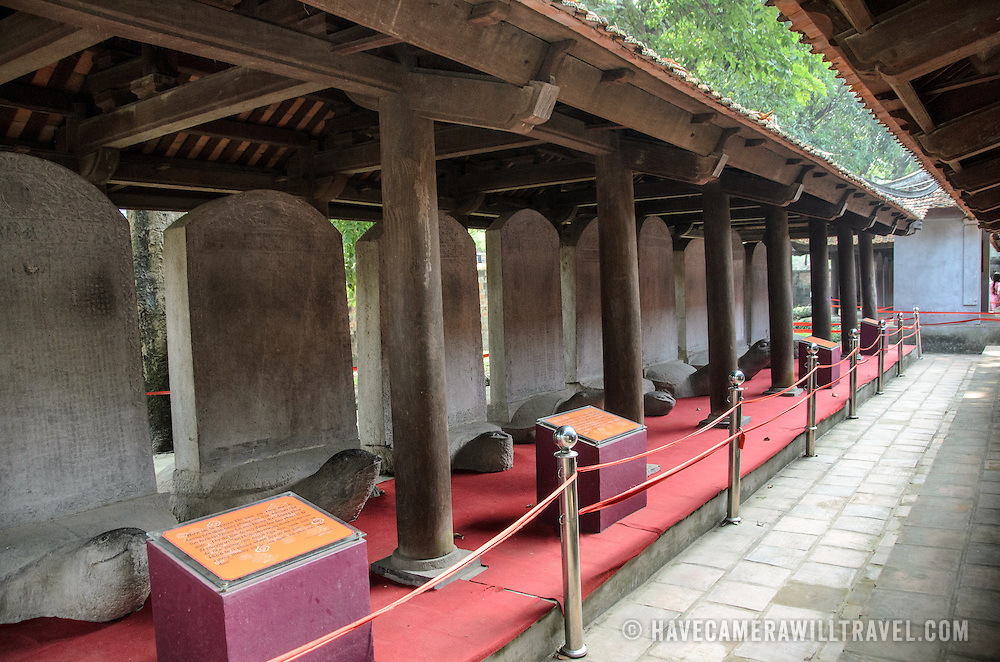 A row of stone stelae, known as the Doctors' Stelae, in the third courtard of the Temple of Literature in Hanoi. Each is inscribed with text. The base of each tablet is a stylized giant turtle, one of the city's main symbols. The temple was built in 1070 and is one of several temples in Vietnam which are dedicated to Confucius, sages and scholars.