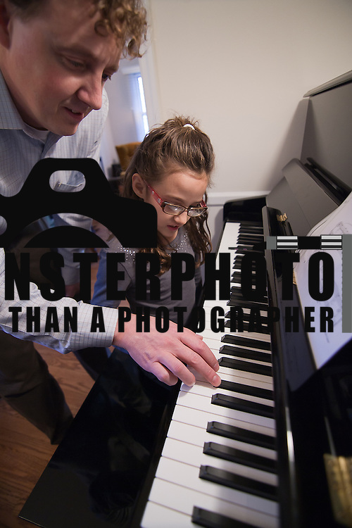 02/03/12 Newark DE: University of Delaware professor Duane Cottrell and his daughter Cason Cottrell (9) practice playing the Hedwig's Theme from the Harry Potter films via the piano together at their home Friday, Feb. 3, 2012 in Newark Delaware...Special to The News Journal/SAQUAN STIMPSON