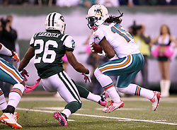 October 17, 2011; East Rutherford, NJ, USA; Miami Dolphins wide receiver Davone Bess (15) carries the ball while New York Jets cornerback Ellis Lankster (26) tries to tackle him during the first half at the New Meadowlands Stadium.