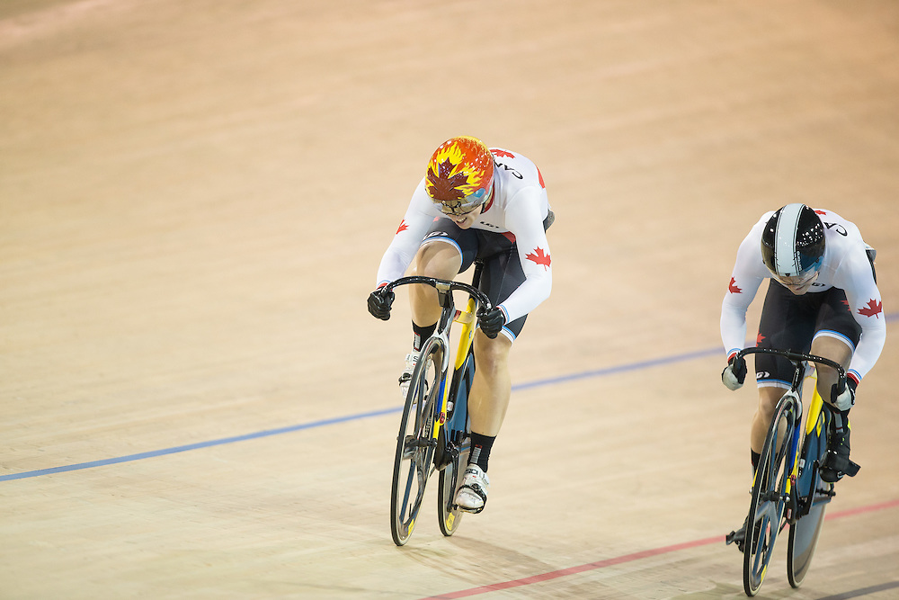 Monique  Sullivan of Canada overtakes teammate Kate  O'Brien in their women's cycling sprint finals at the 2015 Pan American Games in Toronto, Canada, July 19,  2015.  AFP PHOTO/GEOFF ROBINS
