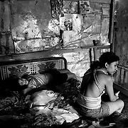 "May 17, 2005 - Managua, Nicaragua - Ivania Gonzalez, 16, right, and Rozievel, 15, both child prostitutes sit together on the bed in the room they share. When Ivania was 12, she was raped by a cousin. ""This life is not happy and not nice.I can do it now but probably not later. I don't like this life. It's for money to pay for my classes. In four months I graduate. I'm trying to see if I can buy a small house and make my own beauty business. I want to study computer engineering."".   ""Sometimes we rest two days, sometimes we come out every night. I used to live with my grandmother. I left the house and they don't know what I do. I don't want to worry them.""."