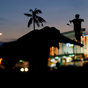 A boy plays on an elephant statue in Phnom Penh, Cambodia.