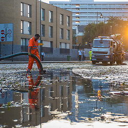 London, UK - 19 September 2014: the sun sets as a workman uses a suction pump on Wick Road. Torrential rains have caused floods and travel disruptions in East London.