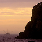 A shrimp trawler returns home to Bandon-by-the-Sea, Oregon, at dusk. The shrimp boat is passing by a large coastal rock formation jutting into the Pacific Ocean. Bandon-by-the Sea is a small town in the Pacific Northwest about 90 miles from Portland, Oregon. It is famous for fishing, crabbing, birding and surfing. This scenic town is located on the Southern Oregon Coast where the Coquille River meets the Pacific Ocean, Bandon, Oregon is 90 miles north of the California border and about nine hours from San Francisco.