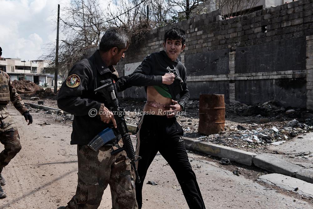Iraq, Mosul: An Iraqi soldier inspect a civilian fearing a suicide attack in west Mosul. Alessio Romenzi