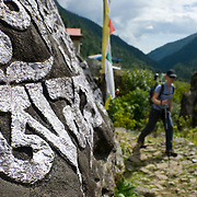 A female trekker passes by giant mani stones near the village of Phakding in the Khumbu (Everest) Valley, Nepal.