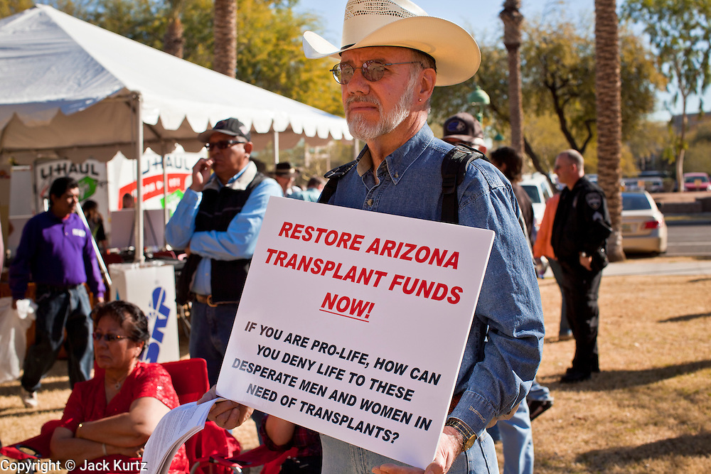 """14 FEBRUARY 2011 - PHOENIX, AZ:  DENNIS HOWERTON, from Maricopa, AZ, pickets Gov. Jan Brewer's speech during Statehood Day observances at the State Capitol in Phoenix Monday. Brewer cut state health insurance funding for medical transplant patients in an effort to balance the state budget. The move has been very unpopular with the public, who have called it the imposition of """"Death Panels."""" So far Brewer has refused to reconsider restoring the cuts. Arizona became the 48th state in the United States on Feb. 14, 1912. Gov. Brewer announced that the state is planning a series of centennial events leading up to Feb 14, 2012 for the coming year during her speech at the state capitol Monday morning.    Photo by Jack Kurtz"""