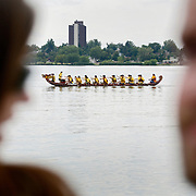 SHOT 7/28/2007 - A Dragon Boat races toward the finish line between a pair of spectators at Sloan's Lake in Denver, Co. during the 2007 Colorado Dragon Boat Festival. The sport of Dragon boat racing is over 2000 years old and features teams of 18 paddlers - nine men and nine women plus someone to steer the boat all rowing to the beat of a drum and racing to a flag 200 meters away on Sloan's Lake in Denver, Co. Founded in 2001 to celebrate Denver?s rich Asian Pacific American culture, the Colorado Dragon Boat Festival has become the region?s fastest growing and most acclaimed new festival. Festival-goers get to explore the Asian culture through demonstrations, crafts, shopping, eating, and the growing sport of dragon boat racing. .(Photo by Marc Piscotty / © 2007)