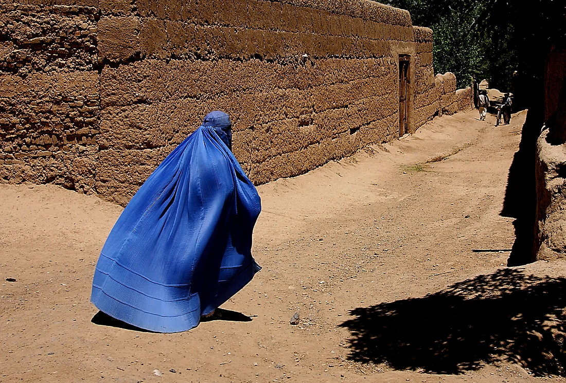 An Afghani woman hurries through the streets of Gardez, as a U.S. military convoy passes her on their way to Bagram, Afghanistan, on May 11, 2002, in support of Operation Enduring Freedom. The convoy is on its way back to Bagram after dropping off members from the 345th Psychological Operation Company, Dallas, Texas, in Gardez. The team will be the first in the area completing their mission of visiting local villages and towns promoting Afghanistan and American coalition cooperation and to gather intelligence. — © /