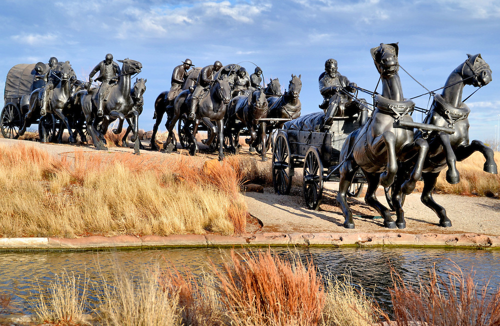 Oklahoma Centennial Land Run Monument in Oklahoma City, Oklahoma<br /> When a cannon was fired at noon on April 22, 1889, 50,000 people scrambled to homestead their piece of two million acres of available land during the Oklahoma Land Rush. That historic event is commemorated in the Bricktown District of Oklahoma City with spectacular bronze statues by Paul Moore. This photo shows the first pieces created in 2003. By 2015, the Land Run Monument included 45, 1 &frac12; size sculptures of horses and covered wagons all fighting to claim the choicest land parcels previously owned by Native Americans.