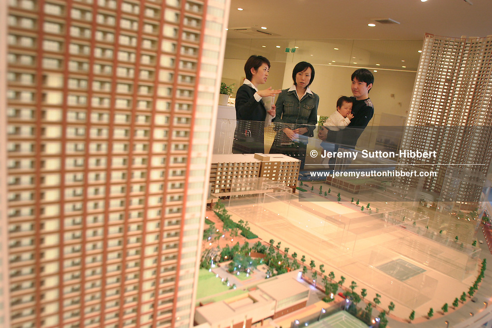 Masaki Isozu (holding baby Erin), and wife Mikiko (centre), with a sales representative,  looking at models and information boards of the Shibuara Island housing development, a new 3 block upmarket residential towers being built in central Tokyo, Japan. 26.03.06