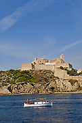 Small fishing and sailing boat in Ibiza, with the castle and city walls in view