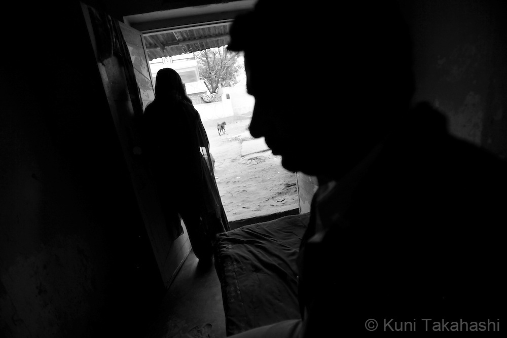Preeti, 23, from Ingonia, stands at the entrance of her room as her customer sits on the bed in Tilawada, a red light district in Rajasthan, India. Many women from Ingonia stay in the district working as prostitutes..