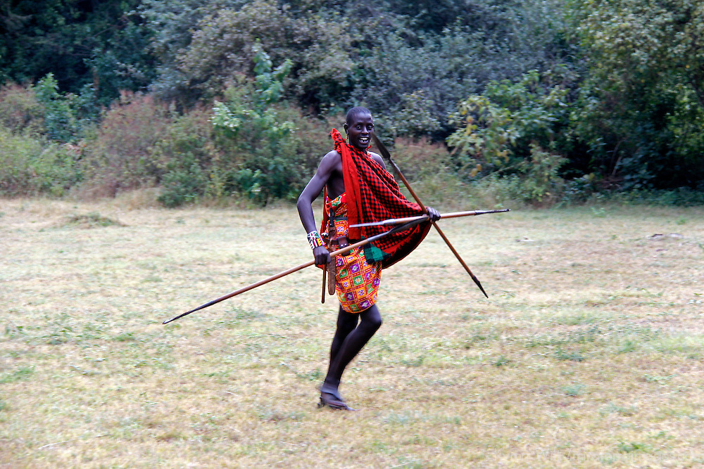 Africa, Kenya, Masai Mara. Maasai Warrior demonstrates spear hunting skills for visitors to Cottar's 1920's safari Camp.