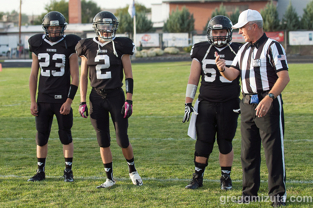 Vale team captains (L to R: Drake Montgomery, Agi Tamez, Tyson Aldred) and head referee Doane Willey before the game with LaGrande, September 20, 2013 at Frank Hawley Stadium in Vale, Oregon. Vale won the game 48-13 to go to 4-0 on the season.