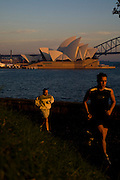Sydney Sites travel series. The Sydney Skyline featuring the Opera House and the Harbour Bridge in the background as early morning runners travel around Mrs Macquaries Chair in Sydney Botanical gardens.