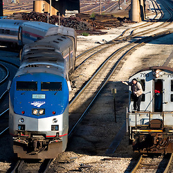 The conductor on the passing switch engine gives a friendly wave as an Amtrak trainset is turned on the Canal St wye.