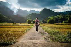 A woman walks on a deserted road, Mai Chau area, Hoa Binh Province, Vietnam, Southeast Asia