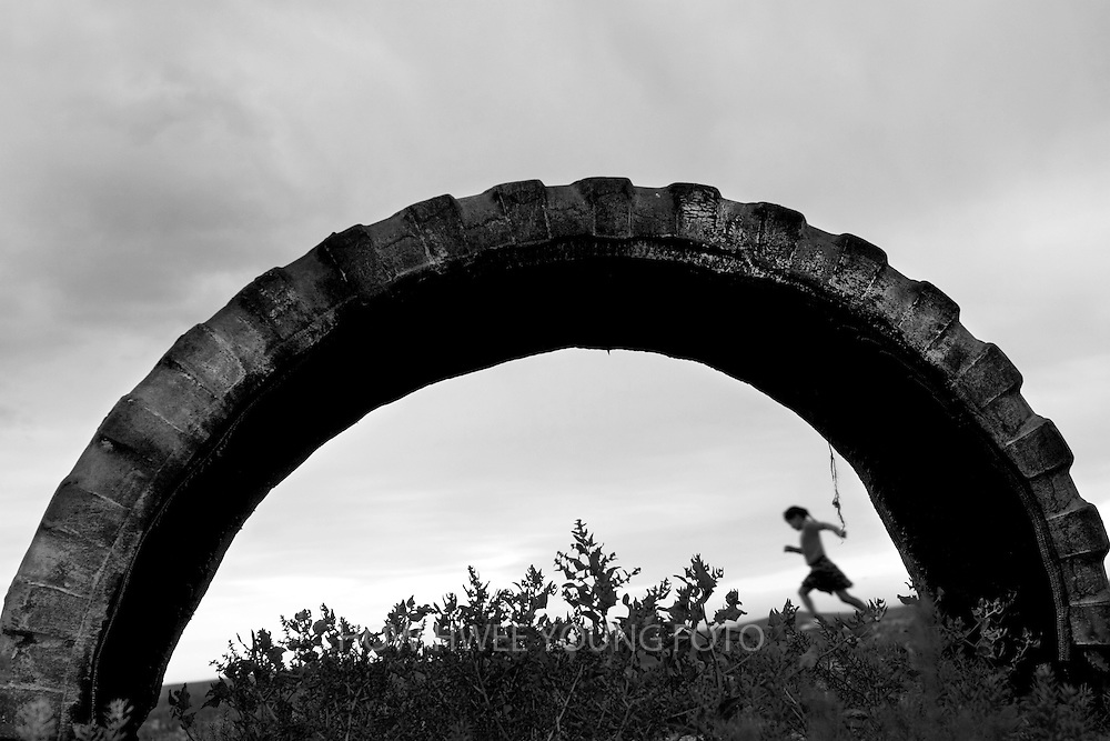 A girl is seen running in the grassland from a discarded tire in Mongolia.