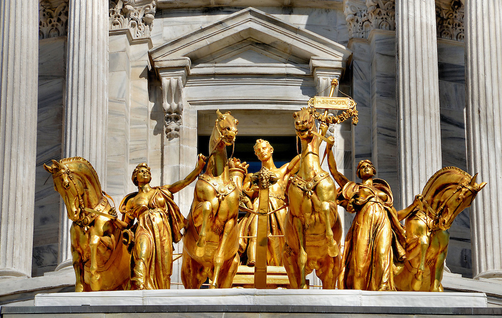 Gilded Quadriga at Minnesota State Capitol in Saint Paul, Minnesota<br /> Atop the south portico of the Minnesota State Capitol in Saint Paul is the gilded Quadriga or &ldquo;The Progress of the State.&rdquo;  The horses represent earth, wind, fire and water.  The women represent civilization yet individually they personify industry and agriculture.  The man symbolizes prosperity.  It was sculpted in 1906 by Daniel Chester French. He is best known for the Abraham Lincoln statue in the Lincoln Memorial in Washington, D.C